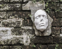 Strange Face Sculpture on a Brick Wall. Unusual and strange face sculpture mounted on an old brick wall Royalty Free Stock Photography