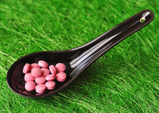 Strange food. Pink pills in a black japanese spoon on a green background Royalty Free Stock Photo