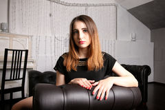 Strange girl in actively searching seated in black leather chair Royalty Free Stock Photography