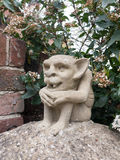A strange goblin gremlin concrete statue on a pillar outside wit. H fangs and big ears creepy scary odd Royalty Free Stock Photo