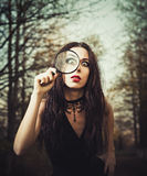 Strange goth girl looks through a loupe Royalty Free Stock Photography