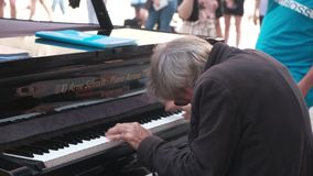 Strange gray-haired senior musician plays jazz on a rare grand piano for tourists on the historic square of the European city. Footage with audio stock footage