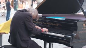 Strange gray-haired senior musician plays jazz on a rare grand piano for tourists on the historic square of the European city. Footage with audio stock video footage