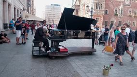Strange gray-haired senior musician plays jazz on a rare grand piano for tourists on the historic square of the European city. Footage with audio stock video