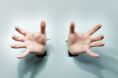 Strange Hands. Coming through holes in a blue cardboard royalty free stock image