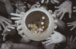 Strange hands hold a pot of coins. Chiang Rai, white temple. Thailand Royalty Free Stock Photography