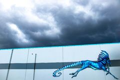 Mural Art of a horse like creature on the side of a building. Strange horse like creature painted on the side of a white building. Deep clouds above providing a Stock Image