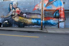 Large mural of two mermaids depicted in street art, Rochester, New York, 2017. Strange but interesting mural of two mermaids clinging together, an expression of Royalty Free Stock Photos
