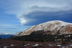 Strange Lenticular Clouds Over a Snow Covered Mountain Top.  Royalty Free Stock Photos