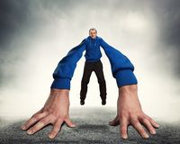 Strange man with big hands. Strange man stands on big hands over grey background Royalty Free Stock Image