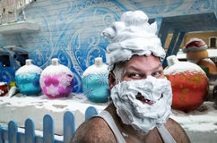 Strange man with covered shaving foam face. Strange smiling man with shaving foam on his face and on his head over winter background Stock Images