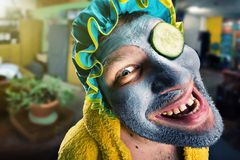 Strange man with face pack. Insane man with face pack in home cosy interior Stock Photo