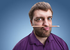 Strange man holds pencil with his nose and lips Royalty Free Stock Photos