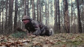 Strange man hunter dressed in camouflage suit crawls on ground like a soldier. Army parody. Forest ranger is fooling