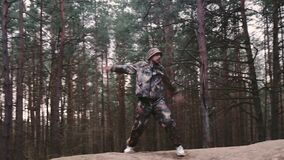 Strange man hunter dressed in camouflage suit dancing techno. Forest ranger 30 year old fooling around. Caucasian