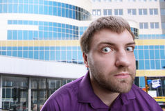 Strange man looks at you. Strange bearded adult man looks at you over building background stock images