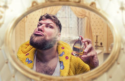 Strange man perfumes himself looking in the mirror Royalty Free Stock Photography