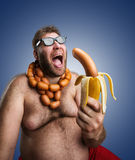 Strange man with sausages. Mad man in glasses with sausages round his neck holds a big wurst in bananas peel over blue Royalty Free Stock Photos