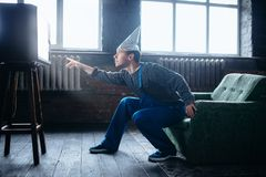 Strange man in tinfoil cap reaches out to TV, UFO. Strange man in tinfoil cap reaches out to the TV, paranoia concept. UFO, conspiracy theory, brain theft Stock Photography