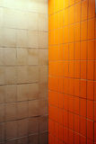Strange meeting of two walls. The meeting of two very diffrent wall covers, strange mix of a public bathroom corner with lighting above Royalty Free Stock Photos