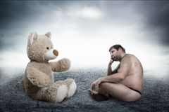 Strange naked man looks at toy bear Royalty Free Stock Photography