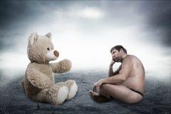 Strange naked man looks at toy bear. On grey background Royalty Free Stock Photography