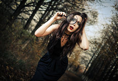 Strange scared goth girl looks through loupe Stock Photos