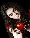 Strange scary girl with mouth sewn shut holds apple studded with nails Royalty Free Stock Photography