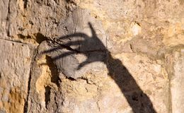 The strange shadow of one hand on an old stone wall. Black shadow, female hand. royalty free stock photos