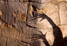 Strange shadow of two hands on an old stone wall. Black shadow, female hand. stock photos