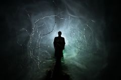 Strange silhouette in a dark spooky forest at night, mystical landscape surreal lights with creepy man. Toned. Strange silhouette in a dark spooky forest at stock image
