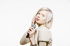 Strange slim blonde girl with a microphone Stock Image