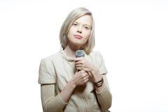 Strange slim blonde girl sing karaoke. With microphone Royalty Free Stock Images