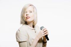 Strange slim blonde girl sing karaoke. With microphone Royalty Free Stock Photos