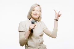 Strange slim blonde girl sing karaoke. And show victory sign Stock Photography