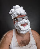 Strange smiling man in glasses. With shaving foam on his face and on his head over grey background Stock Image