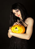 Strange woman in dress holding halloween pumpkin Royalty Free Stock Photography