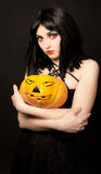 Strange woman holding halloween pumpkin Royalty Free Stock Image
