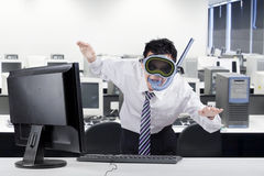 Strange worker with snorkeling equipment. Funny businessman posing to swim in the office while wearing snorkeling equipment with computer on desk Royalty Free Stock Image