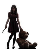 Strange young woman killer holding  bloody knife silhouette. One caucasian strange young woman killer holding  bloody knife an teddy bear in silhouette white Stock Photos
