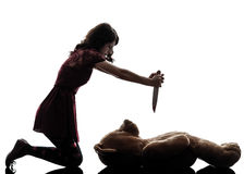 Strange young woman killing her teddy bear silhouette. One caucasian strange young woman killing her teddy bear in silhouette white background stock images