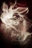 Strangely shaped puff of smoke. On black Stock Images