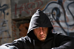 Stranger. Portrait of the man in a hood against an urbanistic wall royalty free stock photos
