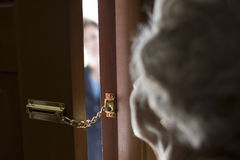 Stranger at the door. Senior woman using a security chain on front door Royalty Free Stock Photos