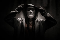 Stranger. Mysterious woman wearing white mask under hoodie,Scary background for book cover Stock Images