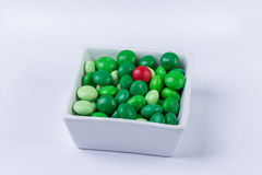 Stranger in our midst. A stranger in our midst - Red chocolate amidst green chocolates Royalty Free Stock Image