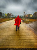 Stranger with a red coat walking at a park on a rainy day against a dramatic sky. Α dramatic and scary scene. Stranger with a red coat walking at a park Royalty Free Stock Photo