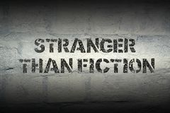 Stranger than fiction. Stencil print on the grunge white brick wall Royalty Free Stock Photo