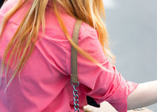 The strap from the bag hangs on the girl`s shoulder Royalty Free Stock Photo