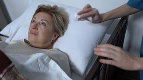 Strappi di pulitura volontari del paziente femminile malato terminale anziano che si trova nel letto di ammalato stock footage